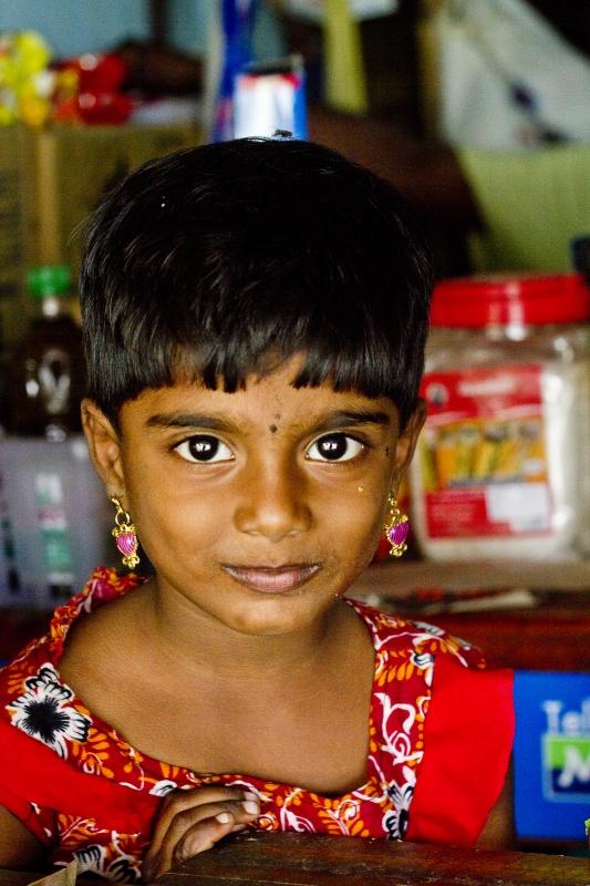 Ta piękna dziewczynka ma na imię Chaturi. Jest Lankijką i mieszka w Dżafnie – stolicy północnej części Sri Lanki. Nie mówi po angielsku, ale bardzo lubi, kiedy robi jej się zdjęcia. Z początku jest trochę nieśmiała, ale kiedy obok stoi jej tata, który zachęca córkę, aby uśmiechnęła się do obiektywu, szybko oswaja się z rolą modelki. Jego obecność dodaje jej odwagi i po chwili przestaje się chować za sklepową ladą. Na co dzień pomaga mu w prowadzeniu sklepu, czasami podaje klientom z lodówki zimne napoje, ale przez większość czasu po prostu obserwuje pracę rodzica i odwiedzających nieduży sklepik klientów. Moja biała twarz ciekawi ją szczególnie, nie widziała pewnie w życiu zbyt wielu blondynek. Ponieważ jej tata nie ma jak mi wydać reszty z tysiącrupiowego banknotu, musi iść rozmienić go do sąsiada, mamy więc czas, aby poprzypatrywać się sobie wzajemnie przez ładne parę minut.